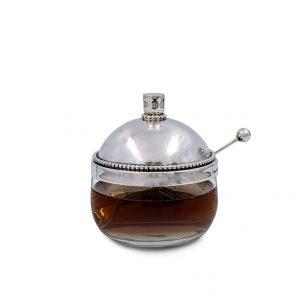 כלי דבש מזכוכית, מהודר במכסה כסף בעיצוב מקורי של מפעלי ביר. המכסה מעוטר פניני כסף וידית אלגנטית. הכלי מגיע עם כפית תואמת, בראשה כדור כסף.